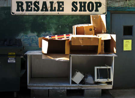 resale: The back of a resale shop empty boxes and a computer the sign on the door reads that no computers should be left.