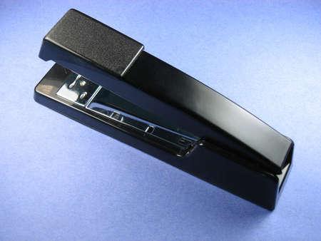 office stapler: Office stapler for stapling Black and stainless steel on blue background