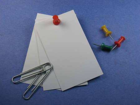 drawing pin: brightly colored drawing pin securing blank cards to background. Plenty of space for your text