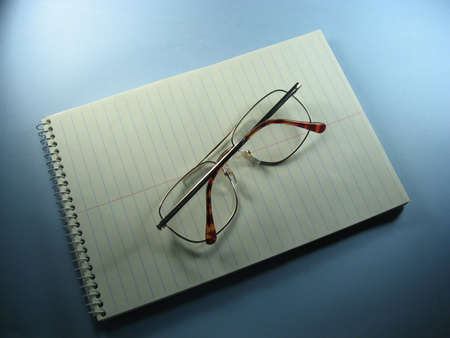 large reading glasses resting on a lined notepad