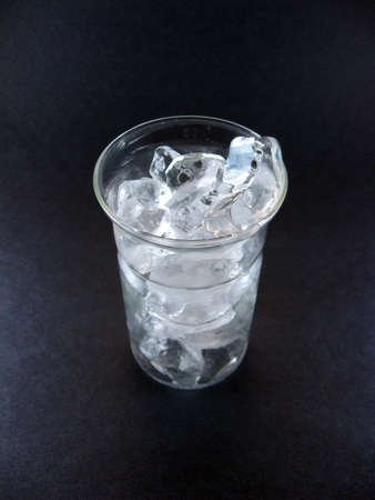 chunks of ice in a drinking glass against colored background