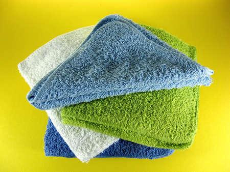 黄色の背景に異なる色の浴用タオル顔の布