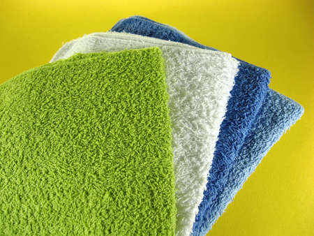 different colored washcloths face cloths on yellow background
