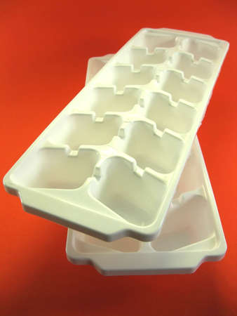 icey: white plastic disposable ice tray on orange background Stock Photo