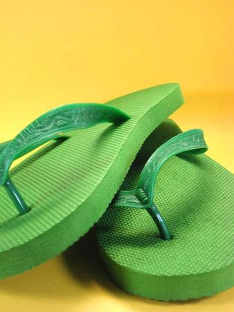 色付きの背景に対する緑色のプラスチック フリップフ ロップ 写真素材