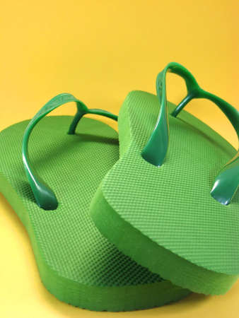 green plastic flip flops against colored background
