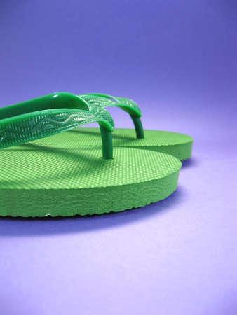 green plastic flip flops against colored background