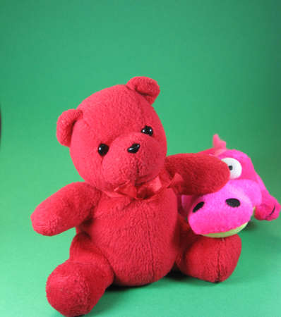 shocking pink small soft toy friendly crocodile and red teddy bear