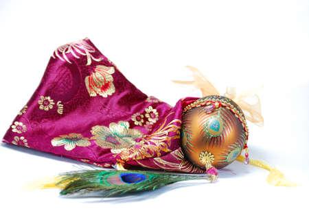 飾られた卵孔雀の羽とバッグの静物画