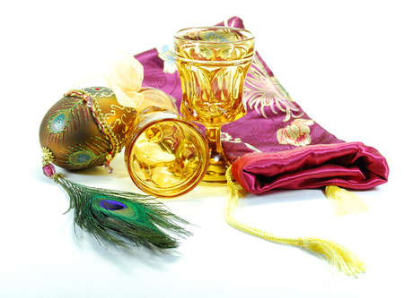 Decorated egg peacock feather drinking glasses and bag still life
