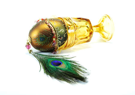 Decorated egg peacock feather and faceted yellow stemmed wine glass
