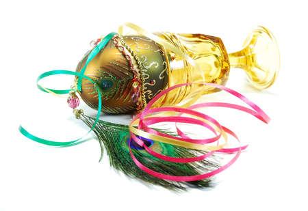 装飾された卵の孔雀の羽とファセットの黄色い茎のワイングラス 写真素材