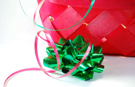 Red basket with festive ribbons and bows as used in wrapping gifts for holiday or birthday
