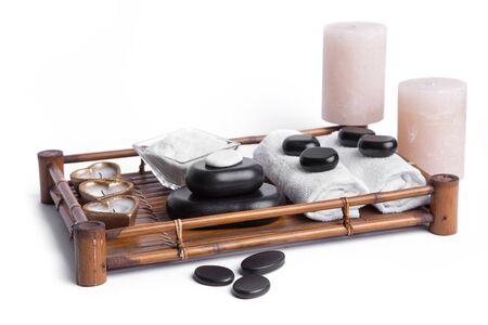 basalt: isolated massage stones set with candles, salt and towels; basalt spa stones on white background