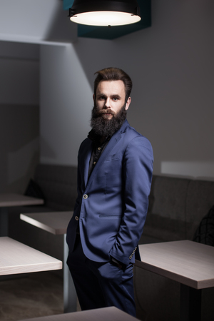 charismatic: charismatic bearded man dressed in suit;