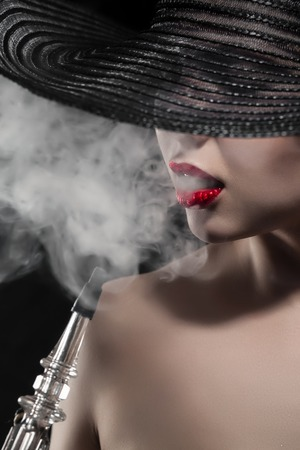 sexy nude girl: beautiful naked girl with red lips smokes hookah on black background; portrait of graceful hookah smoker woman