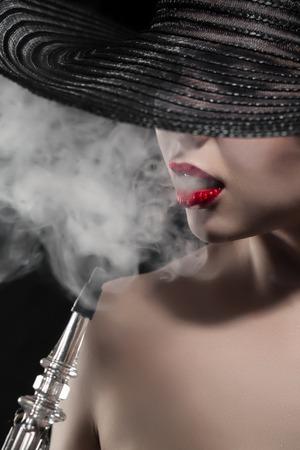 fille sexy nue: belle fille nue avec des lèvres rouges fume le narguilé sur fond noir; portrait gracieux narguilé femme fumeur Banque d'images