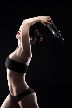 nude girl young: beautiful undressed girl with red lips keeps martini bottle in hands on black background