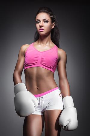 boxeador: hermosa chica sexy vestido con guantes de boxeador; estudio de retrato de la atractiva joven y luchador;