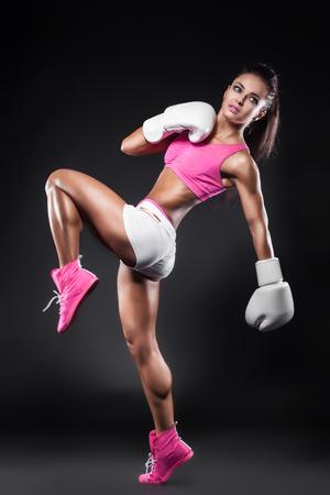 patada: hermosa chica sexy kickboxer vestido con guantes y tomando golpeado por la pierna; retrato de estudio de la mujer atractiva joven luchador haciendo patada;