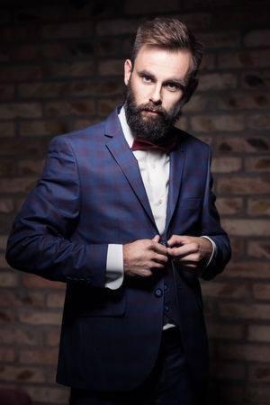 man with beard in suit staying by the brick wall and buttoning; charismatic bearded guy