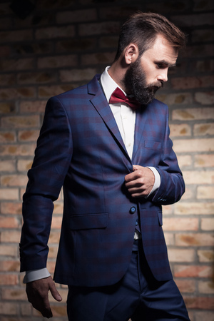charismatic: man with beard in suit staying by the brick wall; charismatic bearded guy