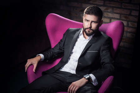 looking into camera: young successful man sitting in chair and looking into camera; real strong gentleman dressed in stylish suit