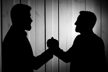 manful: two successful men shake hands; two partners make a deal; businessmen handshake silhouette