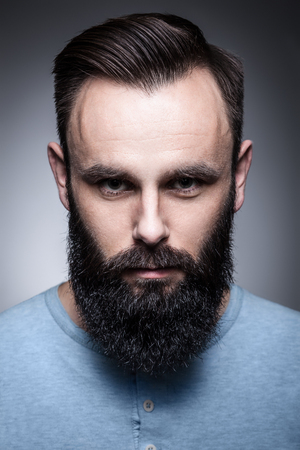 attractive charismatic: hipster with beard and modern hairstyle looking in camera; Stock Photo