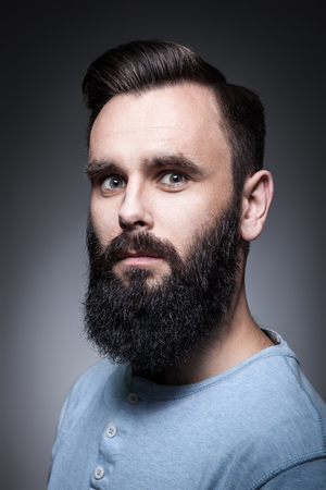 manful: hipster with beard and modern hairstyle looking in camera; Stock Photo