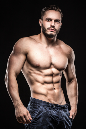 young male: attractive bodybuilder sportsman shows perfect body muscles on black background;