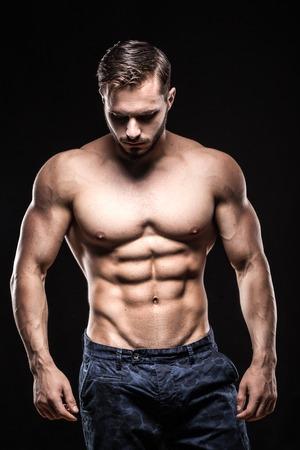 male bodybuilder: attractive bodybuilder sportsman shows perfect body muscles on black background;
