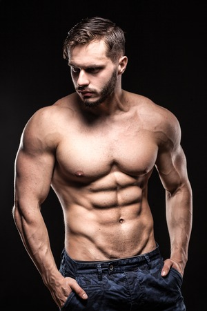 attractive bodybuilder sportsman shows perfect body muscles on black background;