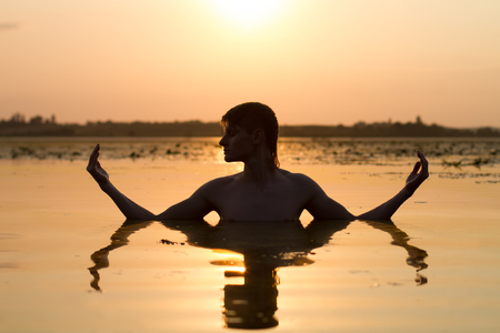 composure: man meditate in water in rays of sun; guy medidate; calmness of sunset on lake; quietness and tranquility; Stock Photo