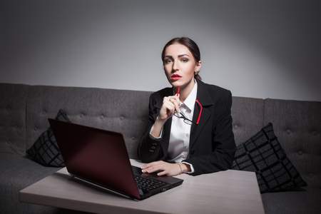 attractive charismatic: businesswoman dressed in suit and with laptop; Stock Photo