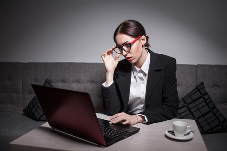 attractive charismatic: businesswoman dressed in suit and with laptop has coffee break; Stock Photo