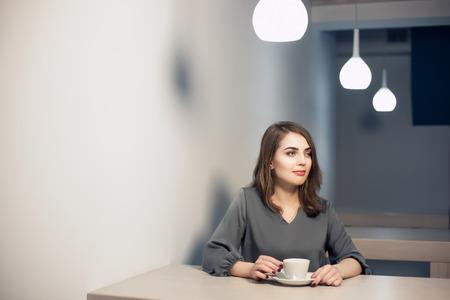 break in: young adult female has coffee break in cafe;