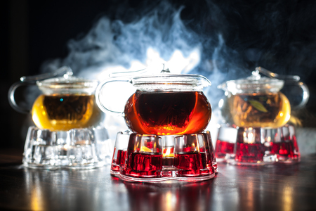 teakettle: three glass teapots with candle heaters and backlighted smoke on background;