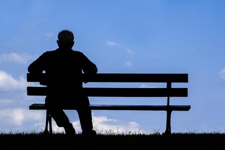 soledad: anciano sentado solo en el banco del parque; silueta de reposo se retiró de alto nivel Foto de archivo