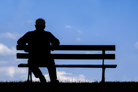gerontology: old man sitting alone on park bench; silhouette of resting retired senior