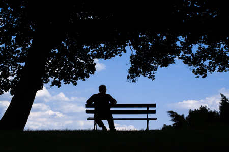 gerontology: old man sitting alone on park bench under tree; silhouette of resting retired senior Stock Photo