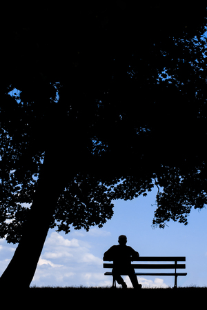 solitariness: old man sitting alone on park bench under tree; silhouette of resting retired senior Stock Photo