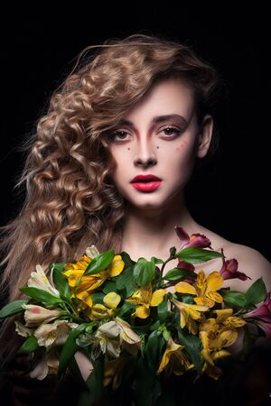 alstromeria: young blonde girl keeps flowers on black background Stock Photo