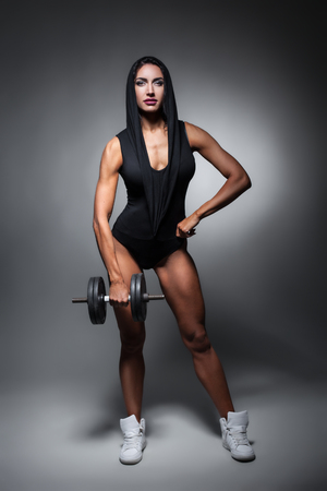 gym dress: fitness woman with sexy muscular body in sexy wear and with dumbbell;