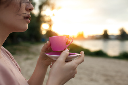 females hands keep cup of coffee near lake or river; woman drinks hot tea on the beach near water in rays of sunset;