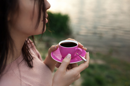coffeetime: female keep cup of coffee near lake or river; woman drinks hot espresso on the beach near water;