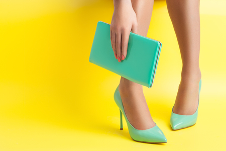 female hand keeps portable turquoise bag on yellow background; sexy woman legs weared in stylish stiletto shoes; Stock Photo