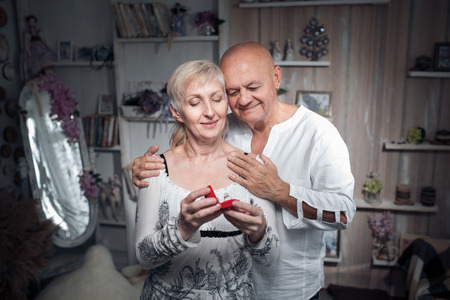 senior man making proposal to older woman; older male hug female and with wedding ring in hand;