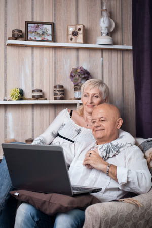 happy seniors couple reading from laptop in cozy room
