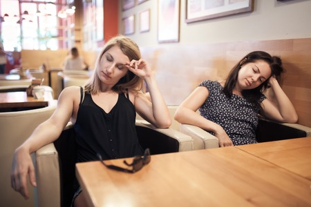 day break: two tired females sitting in cafe and resting; weary girls have coffee break after hard working day; Stock Photo